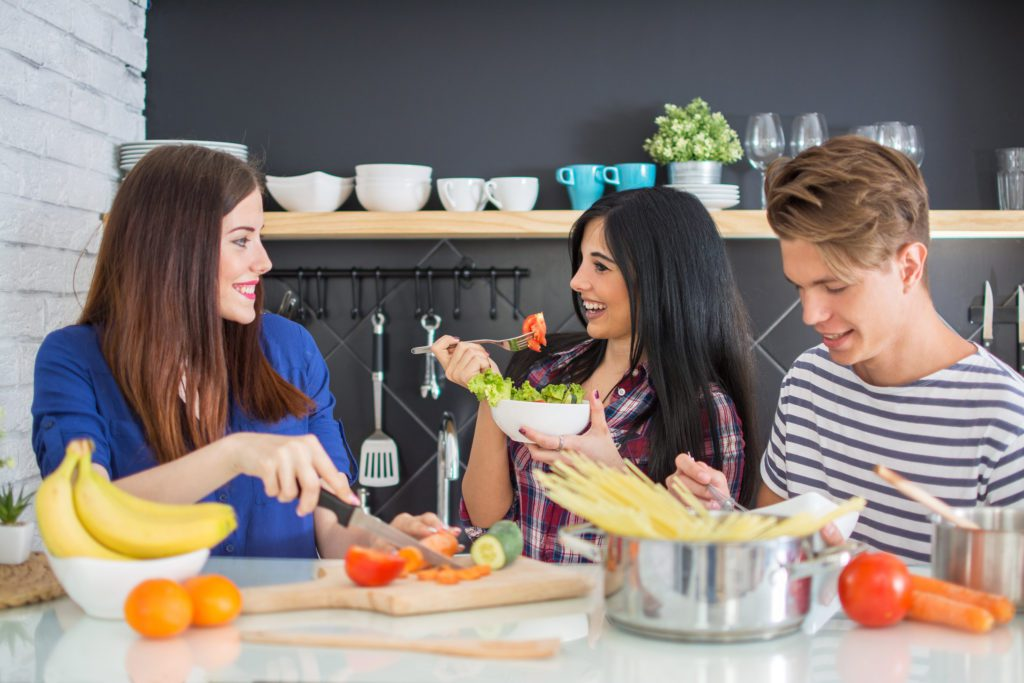 Young Group Of Friends Preparing Vegetable Meal And having Fun